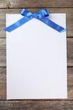 Лист чистого листа бумаги с голубым смычком на серой деревянной предпосылке Стоковое Изображение RF