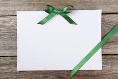 Лист чистого листа бумаги с зеленым смычком на серой деревянной предпосылке Стоковые Фото