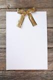 Лист чистого листа бумаги с золотым смычком на деревянной предпосылке Стоковые Фотографии RF