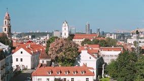 Литва vilnius Взгляд сверху католической церкви St. Johns с колокольней и церковью St Nicholas в солнечном дне лоток видеоматериал