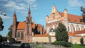 Литва vilnius Люди идя около римско-католической церков St Anne и церков Св.а Франциск Св. Франциск и St Bernard внутри акции видеоматериалы