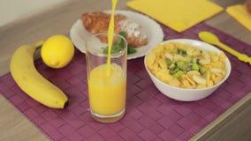 Лить апельсиновый сок в стекле на завтраке видеоматериал