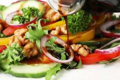 Лить бальзамический уксус на салат овоща стоковые фото