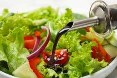 Лить бальзамический уксус на салат свежего овоща в блюде стоковое фото