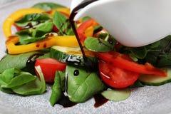 Лить бальзамический уксус на салат свежего овоща на плите стоковое изображение