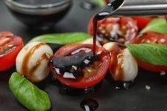 Лить бальзамический уксус на салат свежего овоща на плите стоковые фото