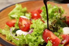 Лить бальзамический уксус на салат свежего овоща на плите стоковое фото rf