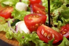 Лить бальзамический уксус на салат свежего овоща на плите стоковые изображения