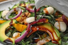 Лить бальзамический уксус на салат свежего овоща стоковое изображение rf