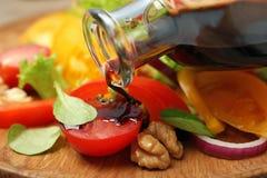 Лить бальзамический уксус на салат свежего овоща стоковая фотография