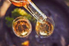 Лить белое вино в стекла на деревянном бочонке стоковая фотография rf