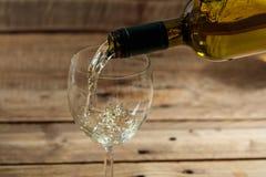 Лить белое вино в стекле на деревянной предпосылке стоковые фото