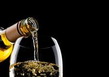 Лить белое вино от бутылки к стеклу на черноте с космосом для вашего текста стоковые изображения