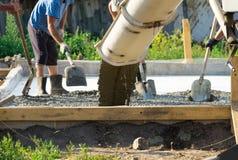 Лить бетон от конкретного смесителя Работа бетона людей лить стоковые изображения