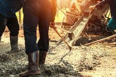 лить бетон с работником смешивает цемент для строя дороги на жулике стоковое фото
