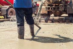 лить бетон с работником смешивает цемент на конструкции стоковое изображение
