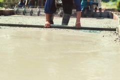 лить бетон с работником смешивает цемент на конструкции стоковое изображение rf