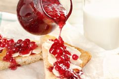 Лить варенье от кувшина на тост с красной смородиной на таблице стоковое фото