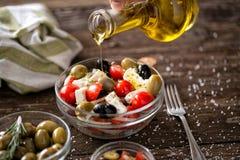 Лить виргинское оливковое масло на вегетарианском салате с свежим vegetabl стоковое фото