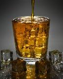 Лить виски выпивает в стекло с кубом льда стоковая фотография