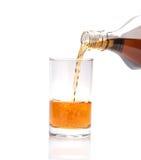 Лить виски в стекло на белой предпосылке стоковое фото rf
