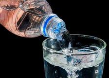 Лить вода к стеклу изолированному на черной предпосылке стоковое изображение rf