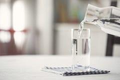 Лить вода к стеклу, кухне, дому Стоковая Фотография