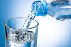 Лить вода от бутылки в стекло на голубой предпосылке стоковое изображение