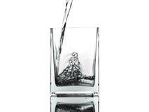 Лить вода в стекло изолированное на белой предпосылке Стоковые Изображения RF