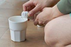Лить вода от бутылки в чашку для доли хорошей Стоковые Изображения RF