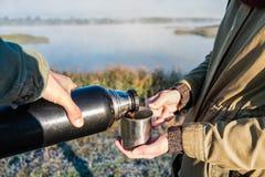 Лить горячий кофе из склянки thermos на красивом берег реки береге реки стоковое изображение rf