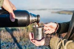 Лить горячий кофе из склянки thermos на красивом берег реки береге реки стоковая фотография rf