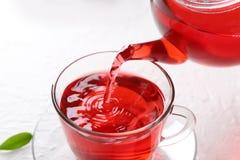 Лить горячий красный чай в стеклянную чашку на таблице стоковая фотография
