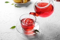 Лить горячий красный чай в стеклянную чашку на таблице стоковое изображение rf