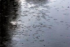лить дождь, с грозой и громом, подачи воды на асфальт формируя бассейны, падения дождя получает к бассейнам и стоковое фото