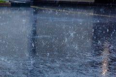 лить дождь, с грозой и громом, подачи воды на асфальт формируя бассейны, падения дождя получает к бассейнам и стоковая фотография