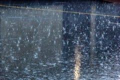 лить дождь, с грозой и громом, подачи воды на асфальт формируя бассейны, падения дождя получает к бассейнам и стоковые изображения