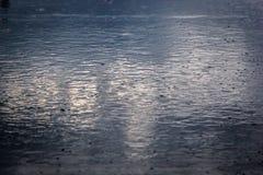 лить дождь, с грозой и громом, подачи воды на асфальт формируя бассейны, падения дождя получает к бассейнам и стоковые фото