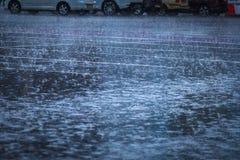 лить дождь, с грозой и громом, подачи воды на асфальт формируя бассейны, падения дождя получает к бассейнам и стоковое изображение