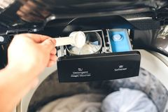 Лить жидкостный тензид прачечной в стиральной машине стоковое изображение rf