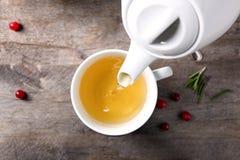 Лить зеленый чай в керамическую чашку на деревянном столе стоковые изображения