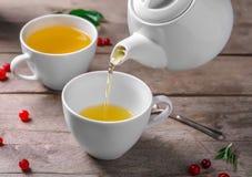 Лить зеленый чай в керамическую чашку на деревянном столе стоковая фотография