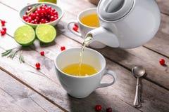Лить зеленый чай в керамическую чашку на деревянном столе стоковые фото