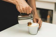 Лить капучино в чашку Стоковое Фото