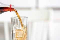 Лить кола от бутылки в стекло на запачканной предпосылке, крупном плане стоковое фото rf