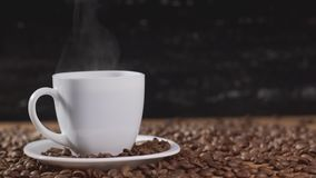 Лить кофе в белой чашке окруженной кофейными зернами на темной предпосылке 4K акции видеоматериалы