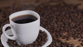 Лить кофе от бака кофе в белой чашке окруженной кофейными зернами в 4k UHD акции видеоматериалы