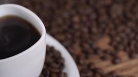 Лить кофе от бака кофе в белой чашке окруженной кофейными зернами в 4k UHD видеоматериал