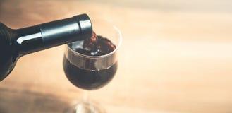 Лить красное вино в стекло на деревянной предпосылке стоковое изображение