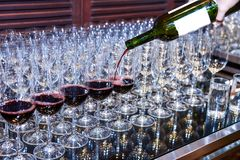 Лить красное вино к стеклам для служения стоковые изображения rf